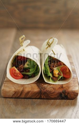 tortilla wrap sandwiches with beef and vegetables on olive board, closeup photo with shallow focus