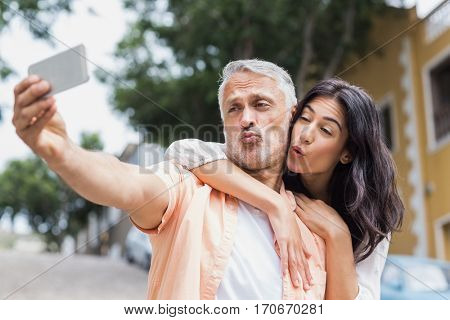 Couple puckering lips while taking selfie in city