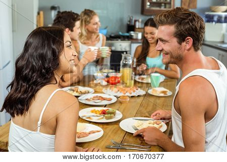 Smiling couple looking at each other while having breakfast with friends at home