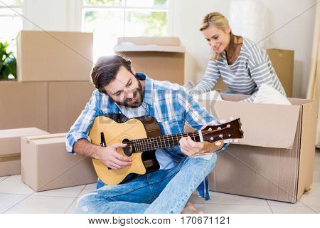 Man playing a guitar while woman unpackaging cardboard boxes in background in their new house