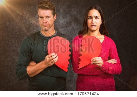 Portrait of serious couple holding cracked heart shape against grey background