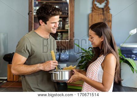 Happy young couple cooking food in kitchen at home