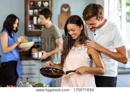 Romantic couple cooking food with friends in background at kitchen