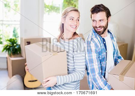 Happy young couple holding cardboard boxes in their new house
