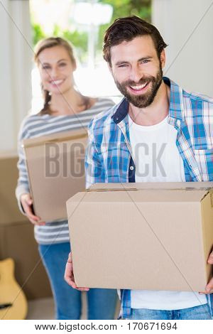 Portrait of young couple holding cardboard boxes in their new house