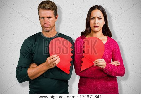 Portrait of serious couple holding cracked heart shape against grey