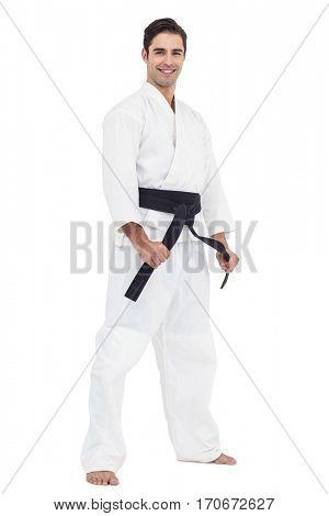 Portrait of fighter tightening karate belt on white background