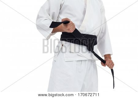 Mid section of fighter tightening karate belt on white background