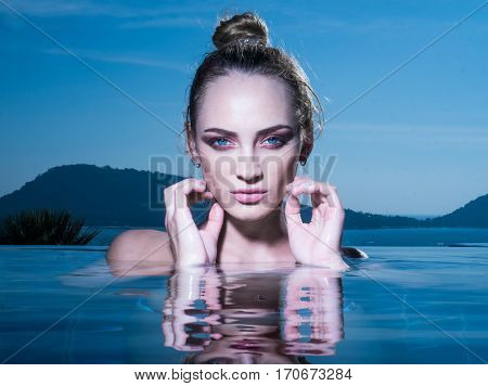 Closeup face of beautiful blond woman standing in the infinity pool over amazing mountain landscape and sky background