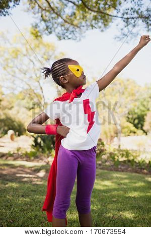 A little girl pretending to fly with superhero costume in the park