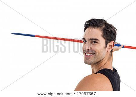 Portrait of happy male athlete holding javelin on white background