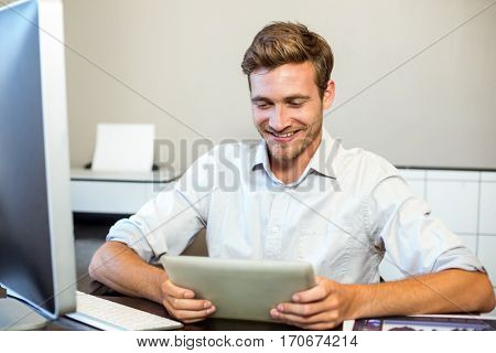 Smiling happy businessman holding digital tablet in office