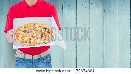 Mid section of delivery man holding box against wooden background