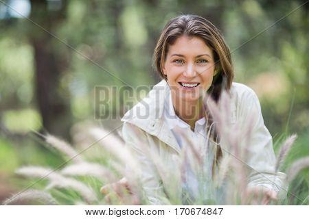 Portrait of beautiful woman crouching on grassy field
