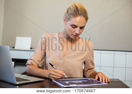 Focused businesswoman writing on document in office