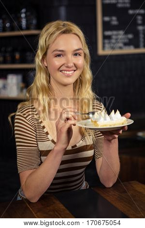 Woman eating cake in a coffee shop