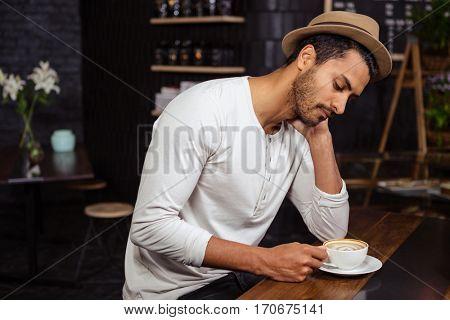 Sad man holding his coffee in a coffee shop