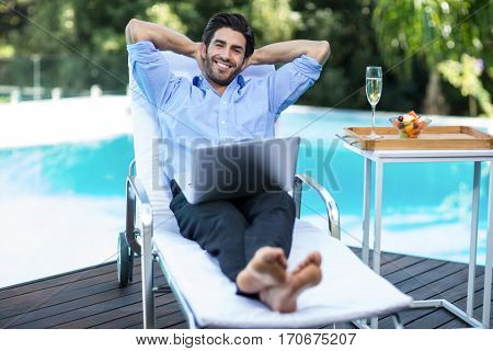 Portrait of smart man with a laptop relaxing on sun lounger near pool