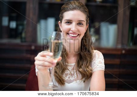 Portrait of happy woman holding champagne flute at restaurant