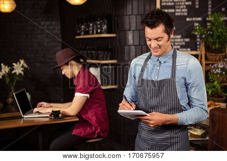 Waiter writing down the orders in a coffee shop