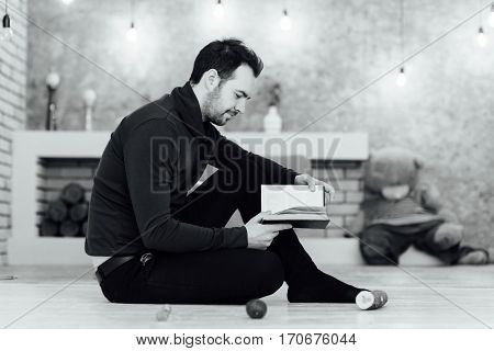 Young Man Reading A Book Seated On Floor At Home