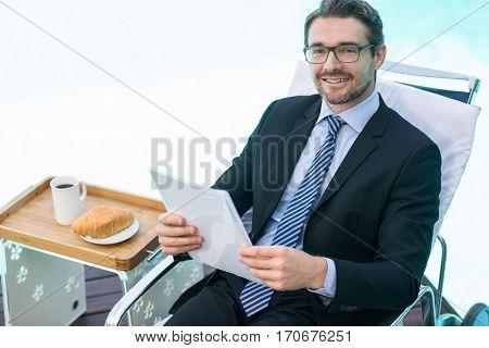 Portrait of smart man relaxing on sunlounger and holding document near pool