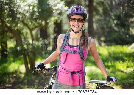 Portrait of joyful woman standing with bicycle against trees at forest