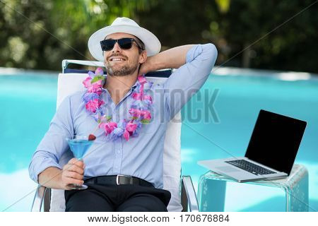 Smart man holding martini glass while relaxing in sun lounger near pool