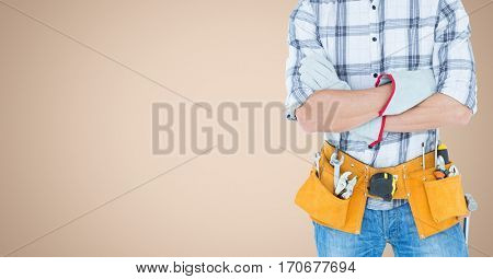 Mid section of handyman with tool belt against beige background