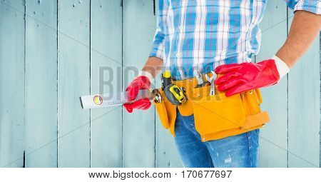 Mid section of handyman with tool belt and sprit level against wooden background