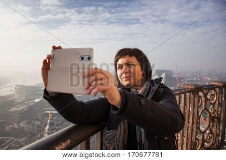 woman taking a selfie from the rooftop of St Paul's Cathedral on a foggy day in London, UK