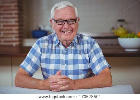 Portrait of smiling senior man with hands clasped while sitting in kitchen
