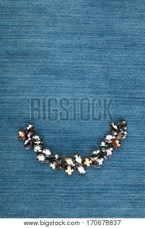 Fashionable background jewelry with rhinestones lying on denim. View from above