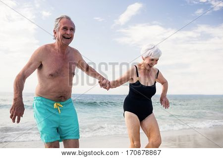 Happy senior couple holding hands and running on the beach at a sunny day