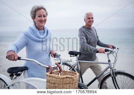 Happy senior couple having ride with their bike on the beach