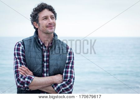 Close-up of confident man looking away while standing at sea shore