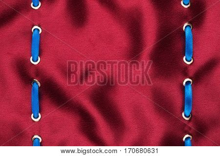 Fashionable beautiful background blue satin ribbon inserted in red satin fabric with space for your creativity. View from above.