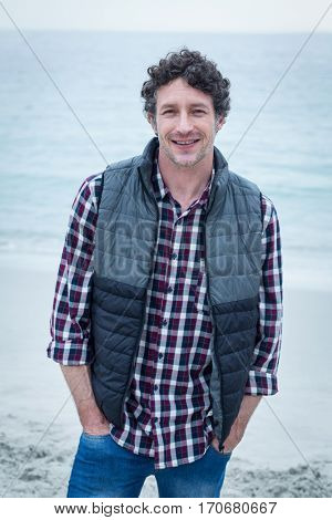 Portrait of confident mid adult man standing at sea hore