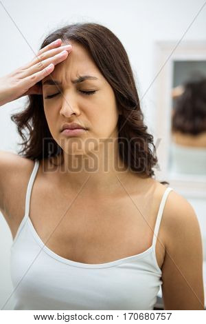 Close-up of young woman getting a headache in bathroom