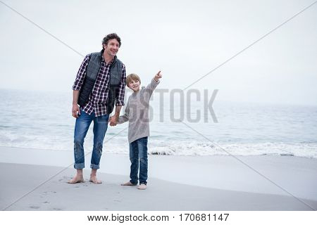 Son pointing while standing with father at sea shore against sky