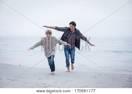 Full length of father and son running on beach with arms outstretched