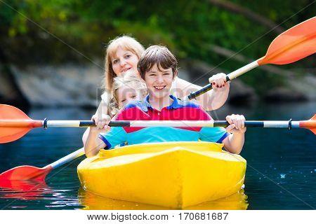 Family Enjoying Kayak Ride On A River