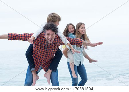 Cheerful parents carrying children at sea shore against sky
