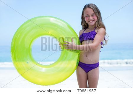 Portrait of cheerful girl holding inflatable ring while standing at sea shore