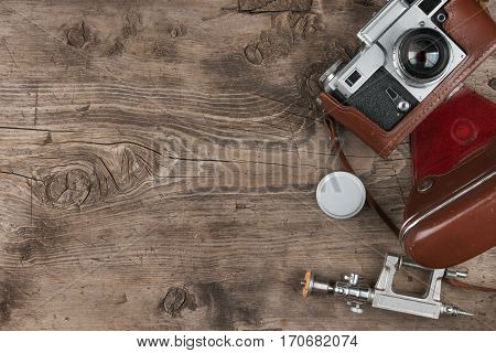 Old photo camera lens cap tripod and brown carrying case on wooden background. Copy space. View from above.