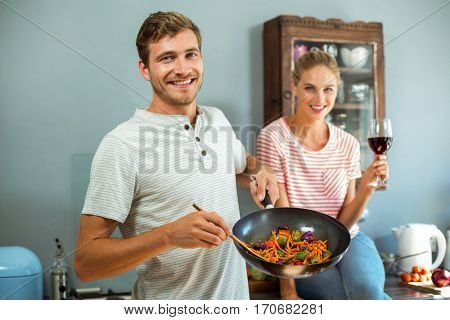 Portrait of happy couple cooking food in kitchen at home