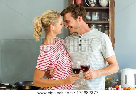 Romantic couple holding wineglasses in kitchen at home