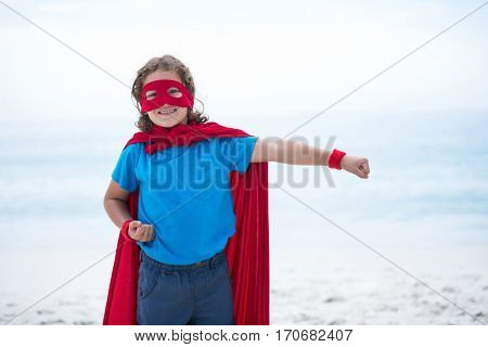 Portrait of boy in superhero costume with clenched fist standing at beach
