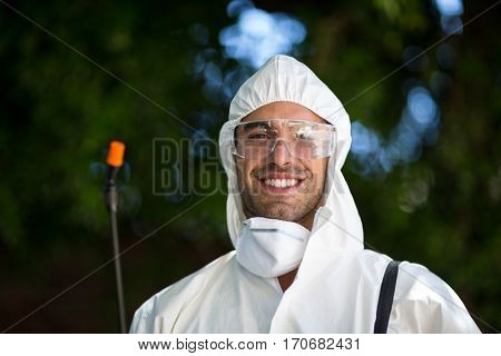 Close-up portrait of smiling man with pesticide sprayer while standing in lawn