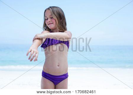 Girl in bikini applying lotion on body while standing at beach